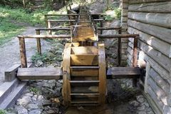 Working water mill wheel with falling water in the village. Sustainable energy and water power traditional machinery.  Stock Images