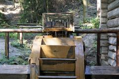 Working water mill wheel with falling water in the village. Sustainable energy and water power traditional machinery.  Stock Photo