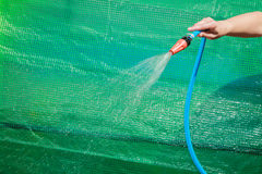 Working watering garden from hose. Watering garden equipment - hand holds the sprinkler hose for irrigation plants. Gardener working royalty free stock image