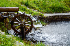 Working watermill wheel with falling waterin the village. Royalty Free Stock Image