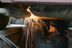 Working welder. Welder and fire sparkles, working under a car Royalty Free Stock Photo