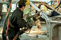 Working welder at the plant for the production of cars. The worker collects the car Stock Photo
