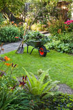 Working with wheelbarrow  in the garden. Evening after work in summer garden with wheelbarrow, shovel and rake - vertical Stock Image