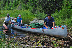 Working through the wilderness. This group of canoers is sliding their canoe across a beaver dam to avoid having to portage the gear.  This is taken in the Stock Photos