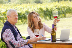 Working at wineries. Portrait of middle age winemaker women holding in her hand a glass of red wine and consulting with senior sommelier while sitting in front Stock Photography