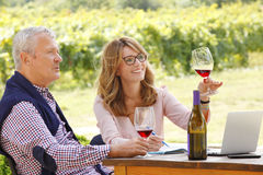 Working at wineries. Portrait of middle age winemaker women holding in her hand a glass of red wine and consulting with senior sommelier while sitting in front Royalty Free Stock Images