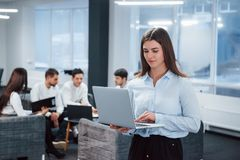 Free Working With Laptop. Portrait Of Young Girl Stands In The Office With Employees At Background Royalty Free Stock Images - 165458699