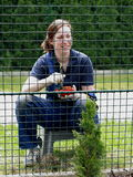 Working woman. Image of a woman painting a fence taken through the fence Stock Images