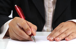 Working woman. Business woman at her office signing a contract with red pen Royalty Free Stock Photos