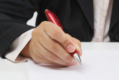 Working woman. Business woman at her office signing a contract with red pen stock image