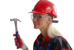 Working woman. A portrait of a pretty blond woman wearing work clothes, hard hat, safety goggles and holding a hammer.  Isolated on a white background Stock Photography
