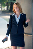 Working Woman in busines suit holding cell phone. Confident Business Woman in Business Suit holding cell phone making sales call Royalty Free Stock Photos