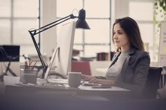 Working woman in front of computer stock images