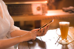 Working woman hands click smart phone at vintage style coffee shop Royalty Free Stock Photography