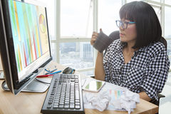 Working woman with hot beverage cup in hand looking to computer Royalty Free Stock Photos