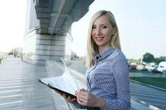 Working woman. Looking at camera. Smiling young business woman holds her documents. Looking  the camera Royalty Free Stock Image