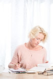 Working Woman Looks at Book while Holding Pencil at Home Stock Photography