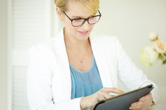Working Woman. Professional elegant woman indoors wearing glasses and working on tablet computer Royalty Free Stock Photo