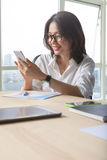 Working woman reading message on smart phone with happiness emot Royalty Free Stock Images