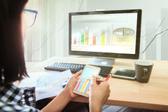 Working woman with smart phone in hand looking to computer busin Royalty Free Stock Photography