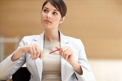 Working woman thinking with a pen in hand Stock Image