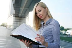 Working woman reading document outdoors. Working woman in the work check  the plan. Business woman reading document Stock Photography