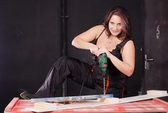 Working woman. Young woman working with drill stock photo