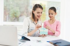 Working woman on maternity leave. The daughter made a present for her beloved mother. Working women on maternity leave. The daughter made a present for her royalty free stock images