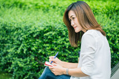 Working women writing at park, working outdoor women work business job Royalty Free Stock Photo