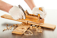 Working with wood plane. Closeup of hands working with wood plane Royalty Free Stock Images