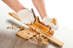 Working with wood plane. Closeup of hands working with wood plane Stock Image