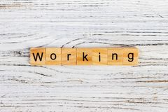 WORKING word written on wood block. WORKING word on block concept Stock Images