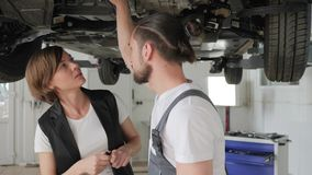 Working at workshop, guy pro advises client, visitor in auto repair, male stock footage