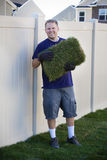 Working in the Yard (Laying Sod). A man works hard to lay new sod grass in his back yard royalty free stock photography