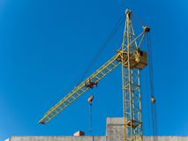 Working yellow crane with the blue sky on the background Royalty Free Stock Images