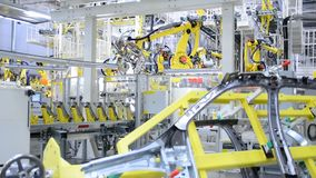 Working yellow robotic arms in the Skoda Auto factory stock video footage