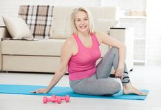 Working with your body. Full length of beautiful middle aged woman sitinding in front of window at home stock images