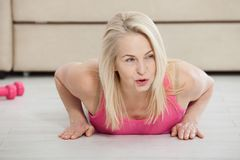 Working with your body. Full length of beautiful middle aged woman in sportswear doing plank while standing in front of Royalty Free Stock Image