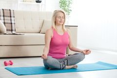 Working with your body. Full length of beautiful middle aged woman in sportswear doing pose lotus while sitinding in Stock Image