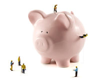 Working on your money. Piggy bank with miniature model workmen, one abseiling down the side with rope Stock Photography
