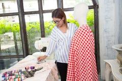 Workingdesigning Kleidung des jungen weiblichen Modedesigners für puppe Stockfotografie