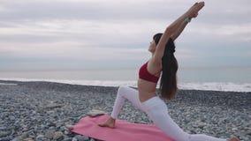 Workiout flessibile della donna su una spiaggia video d archivio