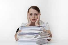 Workload. A stressed female with her head in her hands, sitting at her desk with a large  pile of paper work  stacked in front of her Royalty Free Stock Photos