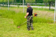 Workman. The workman mows a grass the special tool Stock Image