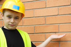 Workman. Boy playing workman in safety vest and hard hat Royalty Free Stock Photography