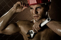 Workman. Closeup portrait  the beauty muscular workman, in red safety helmet  with big   adjustable wrench  in hand, sordid and sweaty Royalty Free Stock Photography