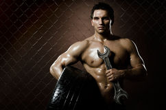 Workman. The very muscular workman with rubber-tire and big wrench,  on  netting  steel fence background Royalty Free Stock Photography