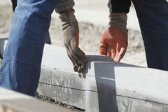 Workman aligning bricks. Close up of workman fitting gray breeze blocks together Royalty Free Stock Photography
