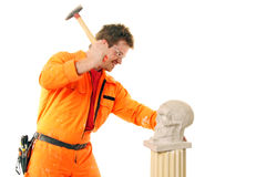 A workman beats a stone skull with a hammer. Isolated on white royalty free stock image