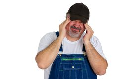Workman in bib overalls with a migraine headache. Grimacing with the acute pain as he rubs his temples with his fingertips in a healthcare and medical concept Royalty Free Stock Photos